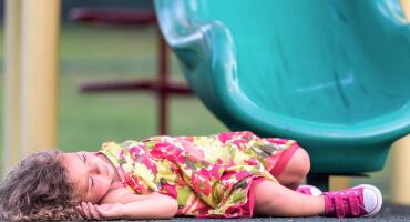 Symbolbild: Kind liegt bewusstlos am Boden neben Rutschbahn